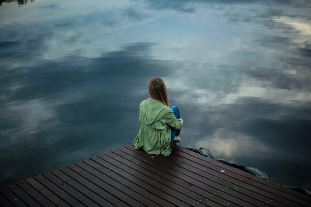 naine istub üksinda veekogu ääres, seljaga kaamera poole